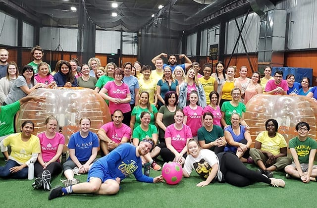 Team of over 30 people pose for the camera after playing bumper ball