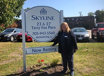 Woman standing next to building sign