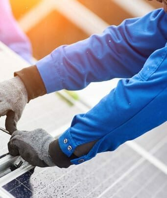 Worker installing a clean energy solar panel system