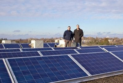 Jason Ashdown, right, COO of Skyline, and Will Beardmore from Bluewater Energy stand among some of the solar panels Skyline has installed on the roof of one of its rental buildings in Guelph.